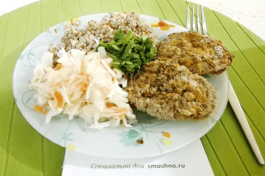 Мясные котлеты с тыквой на тарелке с гречневой кашей и квашеной капустой