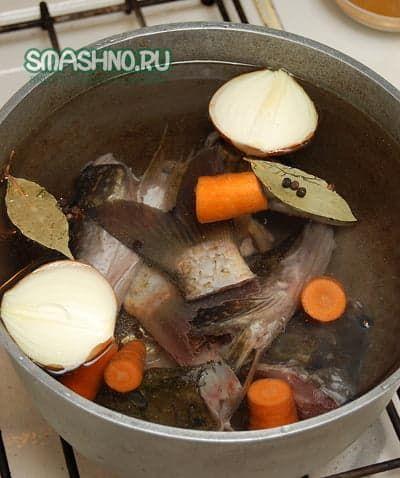Рыба, лук, морковь, лавровый лист, перец горошков в казане с водой