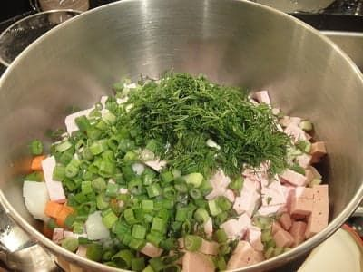 Зелень, нарезанная колбаса в салатнике
