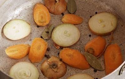 Приготовьте кастрюлю с овощами для фаршированной рыбы