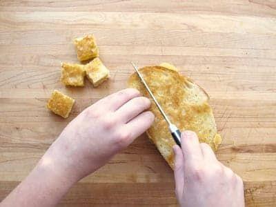 Нарежьте батон с сыром кубиками