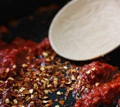 Обжарьте лук, добавьте томатное пюре и специи
