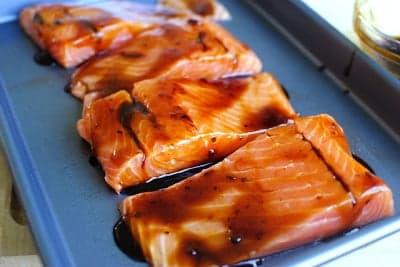 Смажьте кусочки лосося маринадом