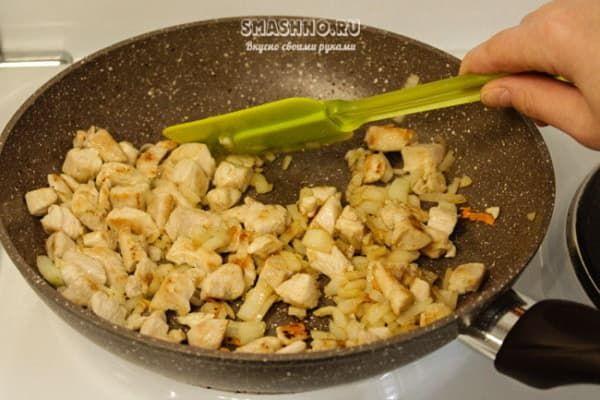 Куриное филе и нарезанный лук в сковороде