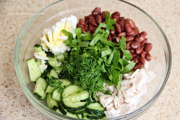 Фасоль, нарезанные огурцы, курица, шпинат в салатнике