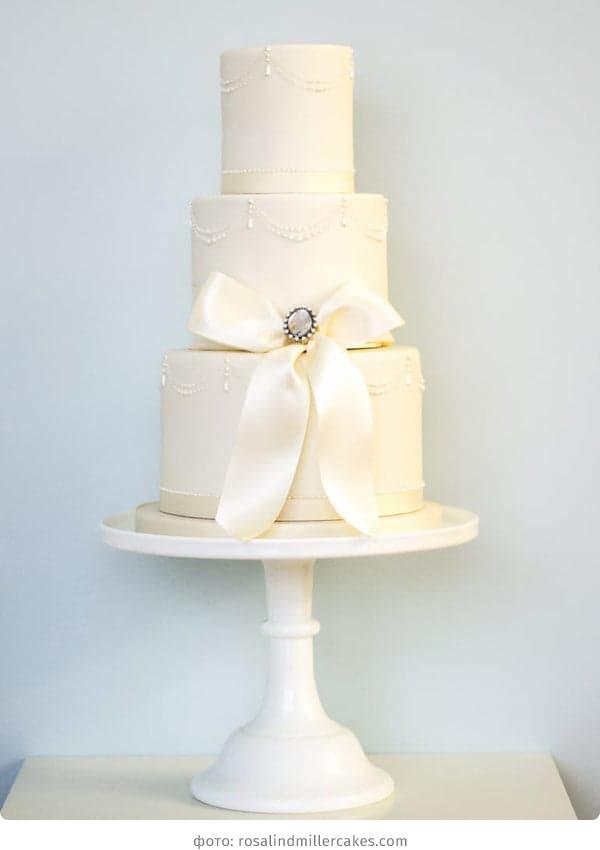 Трехъярусный свадебный торт с бантом из мастики