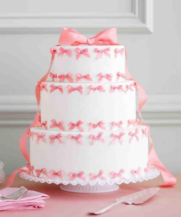 Белый свадебный торт с розовыми бантами