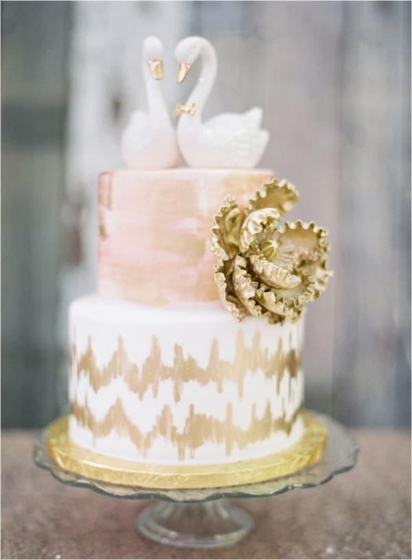 Двухъярусный свадебный торт в нежных тонах фигурками лебедей