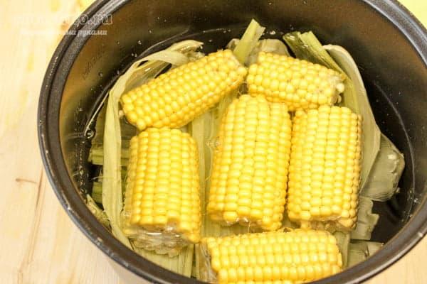 Нарезанные початки кукурузы на листьях в мультиварке с водой