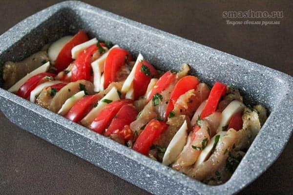Форма для запекания, заполненная кусочками куриной грудки, помидорами и сулугуни